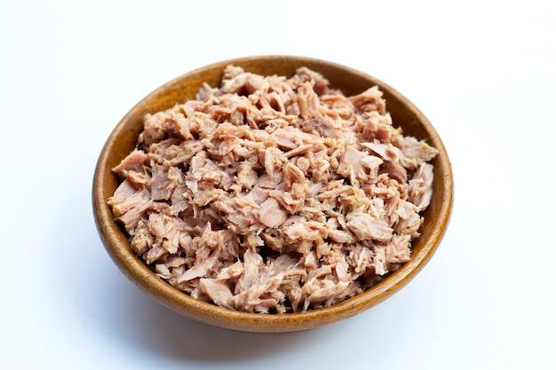 Thunfisch in dosen in holzschale auf weißer oberfläche.