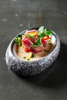 Thunfisch-tartar mit tomaten-zitronen-zwiebel-chili und frischen kräutern im geschirr