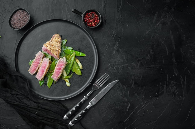 Thunfisch tataki sesam kruste vorspeise mit frühlingszwiebeln und zuckerschoten, auf teller, auf schwarzem stein