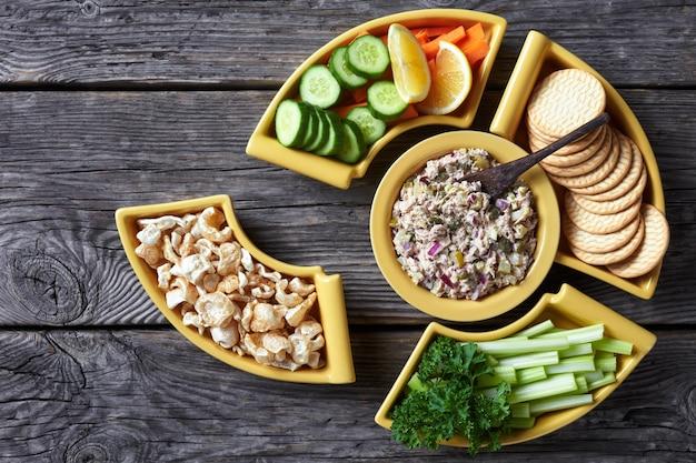 Thunfischkapern essiggurken salat set serviert mit karotten und selleriestangen, geschnittener frischer gurke, crackern und schwarten in gelben schalen auf einem rustikalen holztisch, philippinische küche, flach gelegt