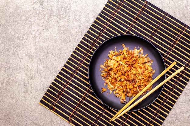 Thunfischrasur im schwarzblech auf bambusmatte und essstäbchen
