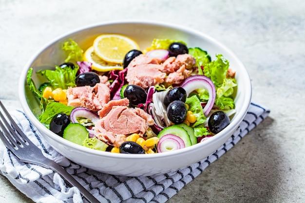 Thunfischsalat mit gurken, mais, oliven und roten zwiebeln in einer weißen schüssel. komfort-food-konzept.