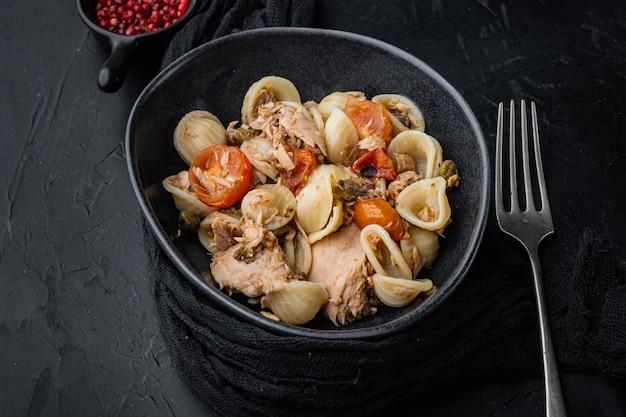 Thunfischsalat mit nudeln und gemüse in der schüssel, auf schwarzem tisch