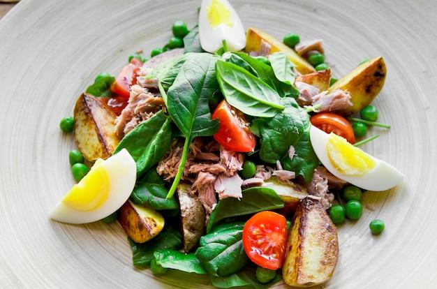 Thunfischsalat mit salateiern und tomaten auf holzteller