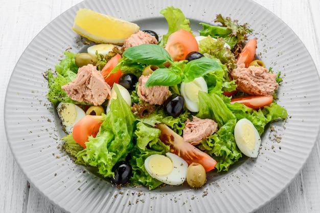 Thunfischsalat mit tomaten, oliven, eiern und zwiebeln.