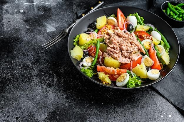 Thunfischsalat nicoise mit gemüse, eiern und sardellen in einem teller. schwarzer hintergrund. ansicht von oben. platz kopieren.