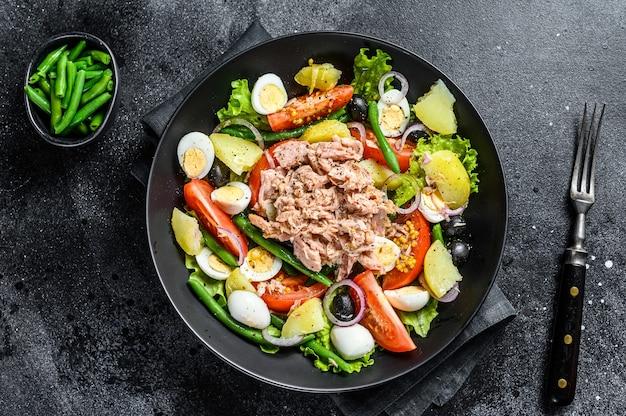 Thunfischsalat nicoise mit gemüse, eiern und sardellen in einem teller.