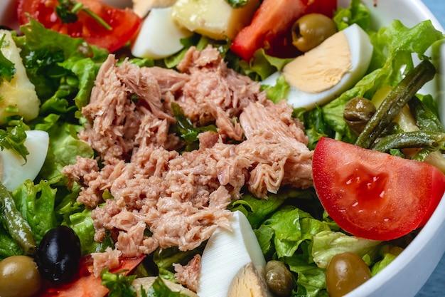 Thunfischsalat von der seite mit gekochtem ei, frischem tomatensalat, grünen oliven und eingelegten kapern