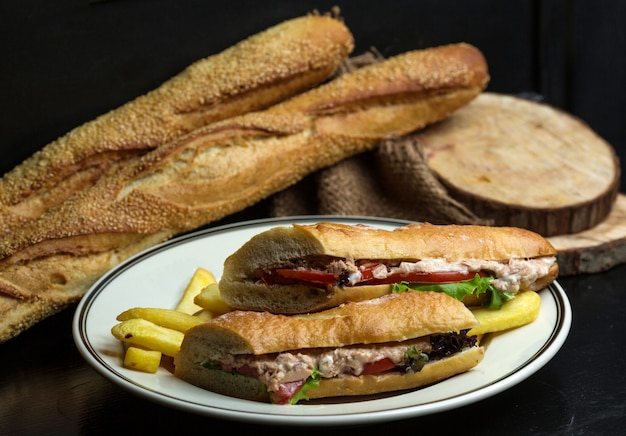 Thunfischsandwich mit mayonnaise, tomate, salat, dazu pommes