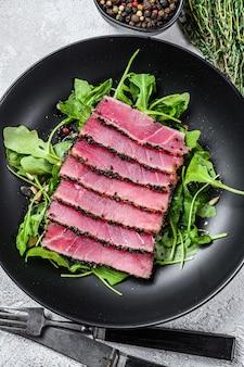 Thunfischsteaksalat mit rucola und spinat. weißer hintergrund. ansicht von oben.