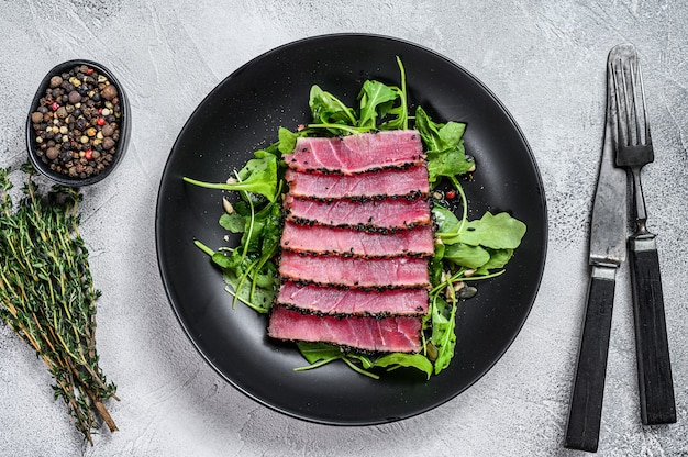 Thunfischsteaksalat mit rucola und spinat. weißer hintergrund. draufsicht.