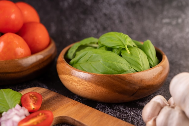 Thymian und tomaten in einer holzschale mit knoblauch auf einem holzschneidebrett.
