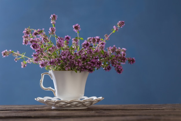 Thymianblumen im weißen weinlesebecher auf holztisch auf blau