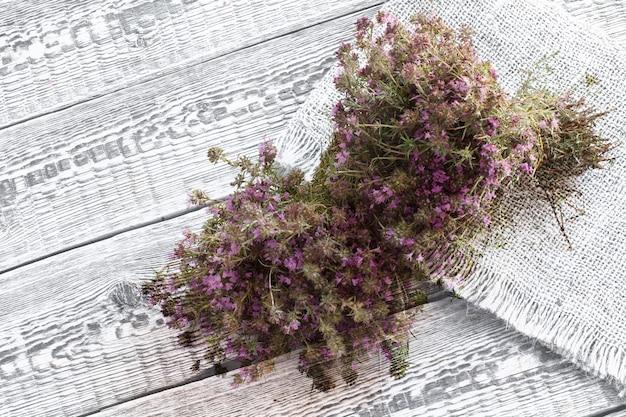 Thymianpflanze mit blüten auf der weißen holzoberfläche