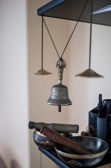 Tibetische instrumente für musikmeditation und silberne glocke hängen mit einer schnur