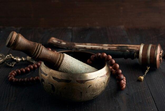 Tibetische singende kupferschale mit einem hölzernen klöppel auf einem braunen holztisch, objekte für meditation und alternative medizin