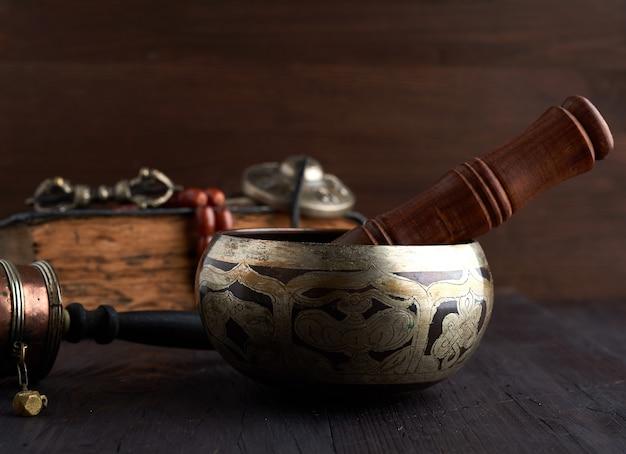 Tibetische singende kupferschale mit einem hölzernen klöppel auf einem braunen umwerben