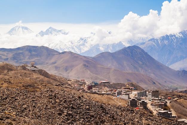 Tibetisches dorf im himalaya-gebirge mit schneebedecktem gipfel