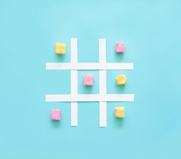 Tic tac toe aus rosa und gelben marshmallows auf blauem grund.