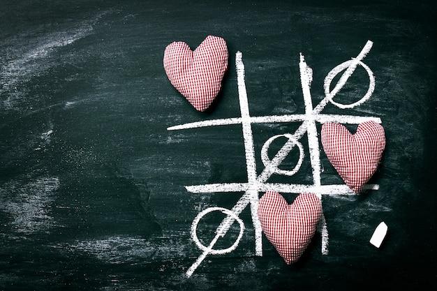 Tic tac toe-spiel. liebe oder valentinstag-konzept mit chalkboar