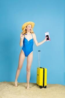 Tickets halten. glückliche junge frau mit tasche vorbereitet für das reisen auf blauem studiohintergrund. konzept der menschlichen gefühle, gesichtsausdruck, sommerferien, wochenende. sommerzeit, meer, meer, alkohol.