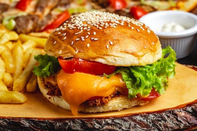 Tief gebranntes hähnchenfilet von seitenansicht mit tomatenkäse und salat zwischen burgerbrötchen