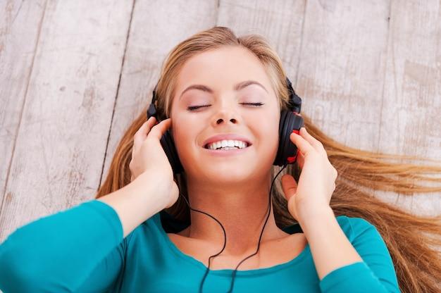 Tief in der musik. draufsicht einer schönen jungen frau, die in ihrer wohnung auf dem boden liegt und musik über kopfhörer hört