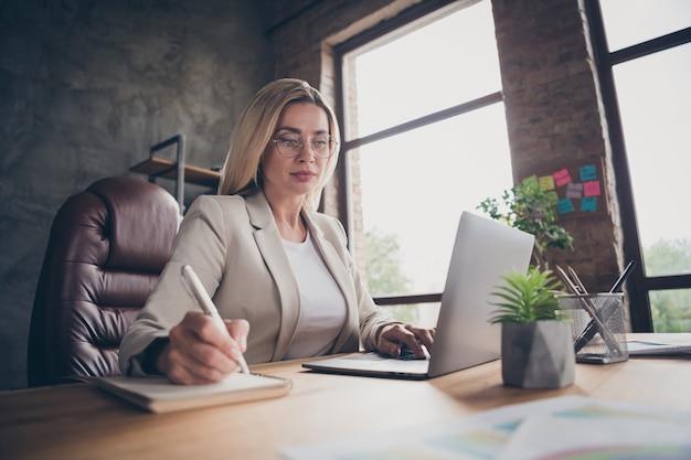 Tief unter dem blickwinkel hübsche unternehmerin, die an berichten für ihren höheren chef arbeitet und die wichtigsten details aufschreibt