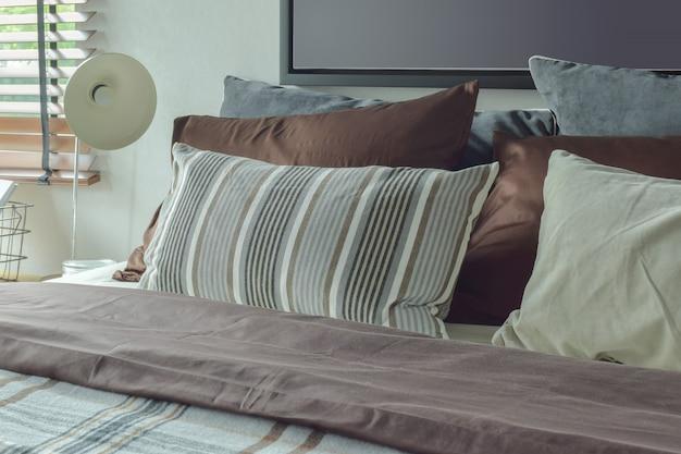 Tiefbraune, graue und weiße bettwäsche und leselampe der modernen klassischen art im schlafzimmer
