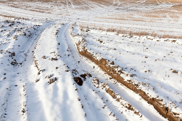 Tiefe rille und spur auf dem weichen boden des feldes, bedeckt mit weißem, reinem schnee, winter