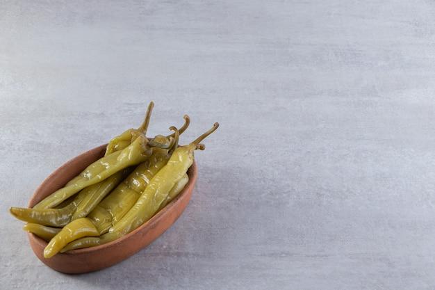 Tiefe schüssel mit fermentierten chilischoten auf steintisch.
