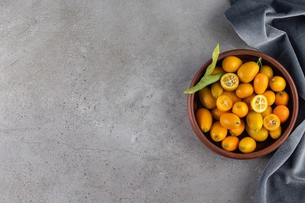 Tiefe schüssel mit frischen saftigen kumquats auf steinoberfläche