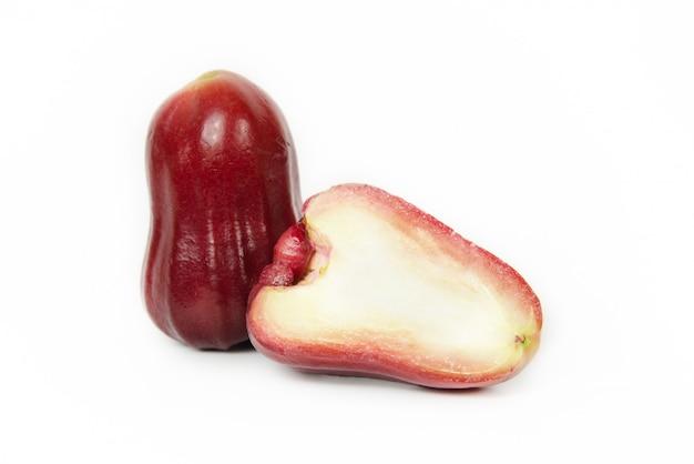 Tiefenschärfe. gruppe rosen-apfel- oder java-apfel- oder syzygiumsamen mit vollem auf hölzernem behälter. isoliert auf weißem hintergrund. fruchtaromen von süßem rotem glanz. frisches obst.