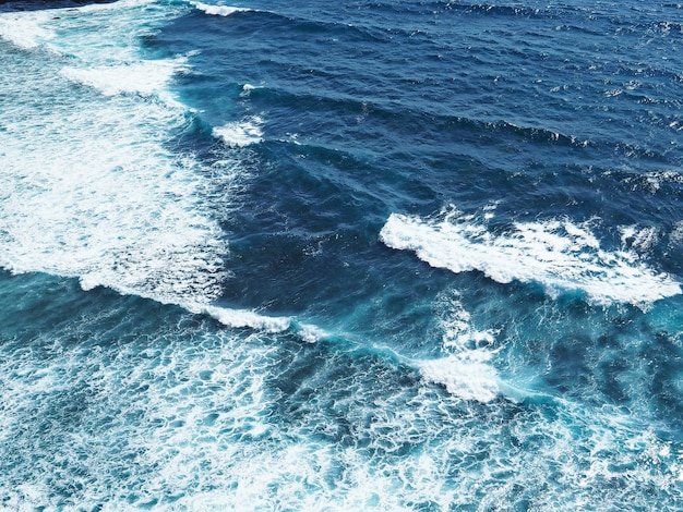 Tiefer blauer ozean mit kleiner wellenbeschaffenheit am sonnigen tag