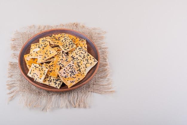Tiefer teller cracker mit schwarzen samen auf weißem hintergrund. foto in hoher qualität