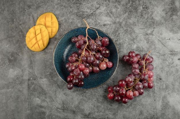 Tiefer teller mit roten reifen trauben und geschnittener mango auf marmoroberfläche.