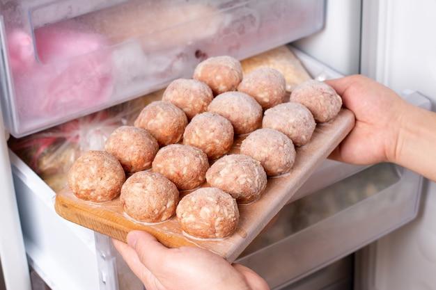 Tiefkühlkost im kühlschrank. plastiktüte mit fleischbällchen im kühlschrank, nahaufnahme