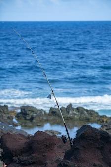 Tiefseefischen am meeresstrand. angelrute hintergrund.