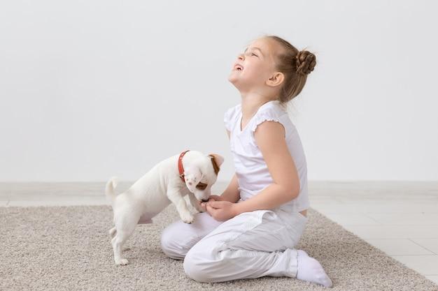 Tier-, kinder- und haustierkonzept - kleines kindermädchen, das auf dem boden mit niedlichem welpen sitzt und spielt.