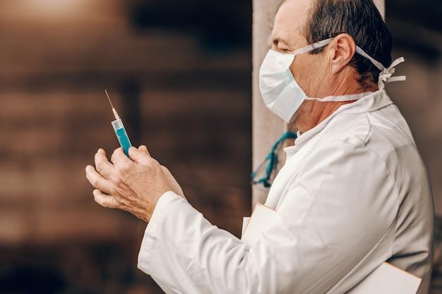 Tierarzt in weißem kittel und schutzmaske beim halten der zwischenablage unter der achselhöhle und vorbereiten der injektion an das schwein.