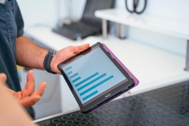 Tierarzt männlich hält einen digitalen bildschirm mit der statistischen grafik aufwachsen.
