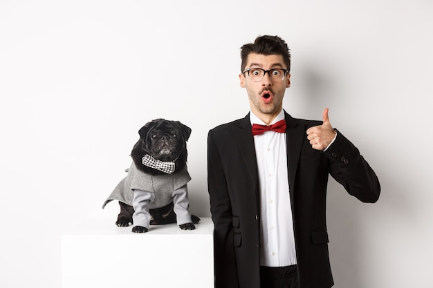 Tiere, party und feierkonzept. hübscher junger mann im anzug und süßer schwarzer mops im kostüm, der in die kamera starrt, besitzer zeigt daumen zustimmend und lobend, weißer hintergrund Premium Fotos
