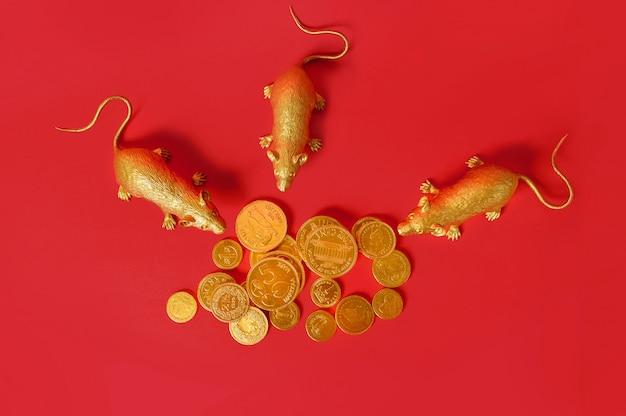Tierkreisgoldratten umgaben eine goldmünze, die mit rotem hintergrund, guten rutsch ins neue jahr gestapelt wurde.