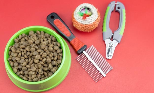 Tiernahrung in schüsseln spielzeug für haustiere auf rotem hintergrund