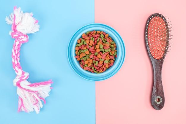 Tiernahrung mit snackknochen für hund oder katze auf farbigem hintergrund