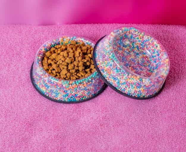 Tiernahrungsschüssel mit futter, verziert mit kleinen farbigen kugeln.