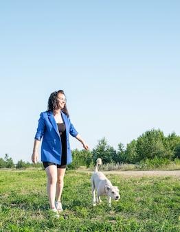Tierpflege. adoption von haustieren. junge frau, die ihren hund im park an einem sonnigen sommertag geht