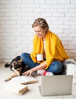Tierpflege. lustige junge frau im gelben plaid, das auf dem boden mit ihren hunden sitzt, die kaffee trinken
