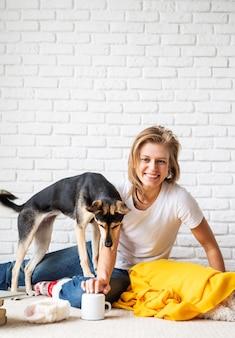 Tierpflege. lustige junge frau im gelben plaid, das auf dem boden sitzt und mit ihren hunden spielt