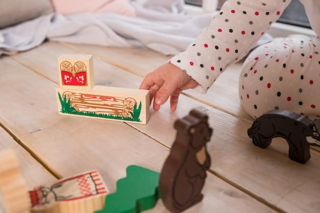 Tierspielzeug kind, das mit dem spielzeug, gemacht von den holzklötzen auf hölzernem beschaffenheitsboden zuhause in seinem raum spielt.